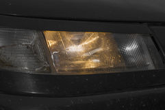 Car included burning amber light. Yellow car headlights shining through the dirty glass Stock Photography