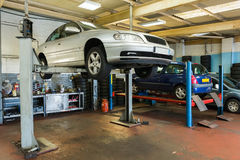 Car inspection. On a service lift in a garage royalty free stock photo