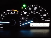 Car instrument panel (30000miles). Illuminated in the night. Car instrument panel showing 30000 miles. Illuminated in the night Royalty Free Stock Photography