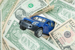 Car insurance. Toy car crashing through a wall of dollars Royalty Free Stock Image
