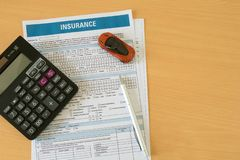 Car insurance concept created using insurance form with Miniature car, calculator and pen on a wooden table stock photography