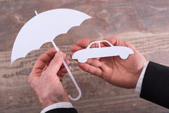 Car insurance concept. Hands holding a car and an umbrella - insurance concept Stock Photography
