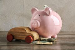 Car insurance concept. Piggy bank and wooden car. On table Royalty Free Stock Photo