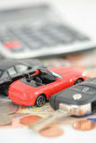 Car insurance concept with toy cars, car key, coins and bills Royalty Free Stock Image