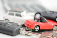Car insurance concept with toy cars, car key, coins and bills Royalty Free Stock Images