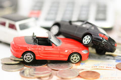 Car insurance concept with toy cars, car key, coins and bills Stock Photos
