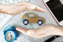 Car insurance concept, woman hands with protective gesture and cardboard car on white background with office objects around royalty free stock photo
