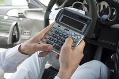 Car insurance cost. Car dealer calculating car insurance for a new car Royalty Free Stock Photo