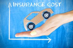 Car insurance cost evolution concept on blue chalkboard with cardboard model car on woman hand royalty free stock image