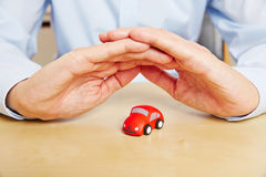 Car insurance with hands over vehicle. Car insurance with hands over red vehicle as a symbol Stock Photo