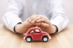 Car insurance. Red toy car covered by hands Stock Photography