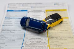 Car insurance report following an accident concept with toy cars on accident statement stock photos