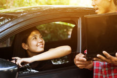 Car insurance. Woman in car smiling to vehicle insurance officer Royalty Free Stock Image