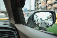 Car interior background with closeup side mirror reflect car, tr. Affic bangkok. image for drive, transport, vehicle, object concept stock photography