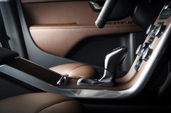 Modern luxury prestige car interior, dashboard, wood panels, steering wheel. Car interior dashboard details, automatic transmission switch Stock Image