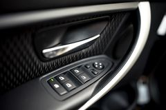 Car interior details of door handle, windows controls and adjustments. Car window controls and details. Car interior details of door handle with windows controls Royalty Free Stock Image