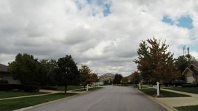 Car interior driving down road looking out front windshield on a cloudy day. A car ride down road in residential suburban neighborhood looking at trees, clouds stock footage