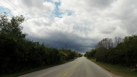 Car interior driving down road looking out front windshield on a cloudy day. A car ride down road in residential suburban neighborhood looking at trees, clouds stock video footage