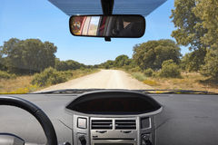 Car interior and gravel road on a sunny day Stock Photography
