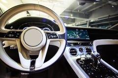 Car interior luxury. Interior of prestige modern car. Dashboard and steering wheel. Focus on steering wheel. Film effect Stock Photography