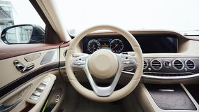 Car interior luxury. Interior of prestige modern car. Leather comfortable seats, dashboard and steering wheel. White. Cockpit with exclusive wood and metal Stock Images