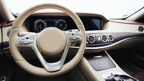 Car interior luxury. Interior of prestige modern car. Leather comfortable seats, dashboard and steering wheel. White. Cockpit with exclusive wood and metal Stock Image