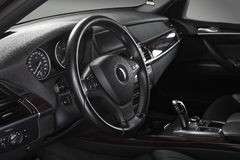 Car interior. Steering wheel. Interior of leather passenger compartment of the car in dark tones Royalty Free Stock Photos