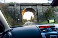 Car interior view of traveling below railroad bridge in UK Stock Photo