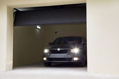Car with its lights on in the garage. Car headlights turned leaves the garage Stock Images