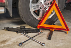 Car jack, lug wrench and safety triangle in a garage Royalty Free Stock Photos