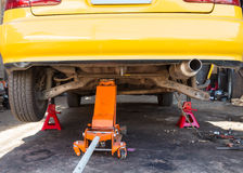 Car with a jack to lift the rear wheel for brake repair. In the garage royalty free stock photo