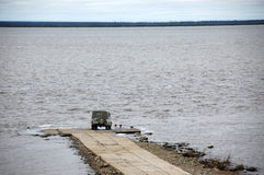 Car at jetty Kolyma river Stock Image