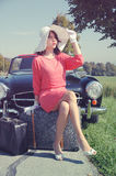 Car journey of the beautiful women, fifties style. Young beautiful woman in fifties style on the road trip, with old car and baggage Royalty Free Stock Photos