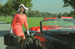 Car journey of the beautiful women, fifties style. Young beautiful woman in fifties style on the road trip, with old car and baggage Stock Photo