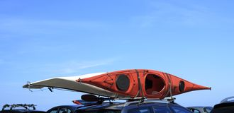 Car with kayak canoe on top blue sky. Active lifestyle Stock Images