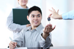 Car key. Happy young man recieving a car key after signing a documant.Focus on the key Stock Photos