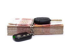 Car key with alarm laying on pile of cash money Stock Images