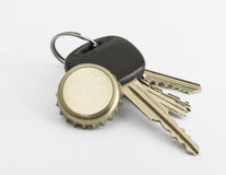 Car key and bottle cap in close up Royalty Free Stock Image