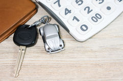 Car key with calculator and wallet. On wood table Stock Image