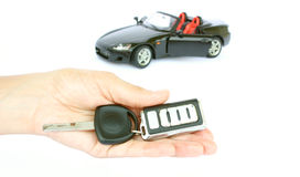 A car key and a car. A hand holding car key and car isolated on a white background Royalty Free Stock Photos