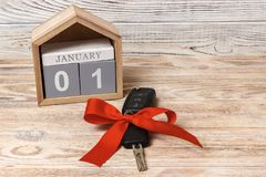 Car key with colorful bow and calendar, on wooden background Stock Photos