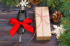 Car key with colorful bow with gift box and christmas decoration on wooden background Royalty Free Stock Images