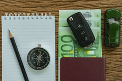 Car key on euro banknotes, passport, compass, pencil, paper note. And miniature car on wood table as travel planning road trip concept Royalty Free Stock Images