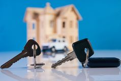 Car key and house keys with new automobile and home Stock Photos