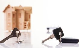 Car key and house keys with new automobile and home Royalty Free Stock Photo