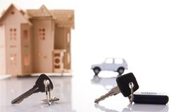 Car key and house keys with new automobile and home Stock Photo
