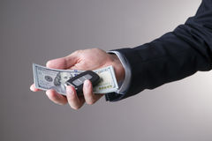 Car key and hundred-dollar bills in the hands of a businessman. On a gray background Royalty Free Stock Images