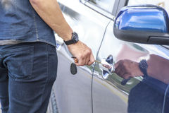 Car key inserted into the lock hole. Transportation and ownership concept - man with car key outside royalty free stock photo