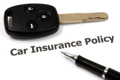Car key on an insurance policy. With pen on white Royalty Free Stock Images