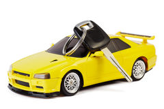 Car key lays on the yellow toy car Royalty Free Stock Photos